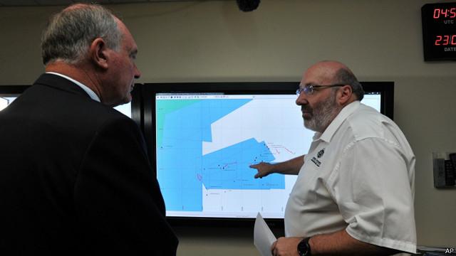 Mike Barton, que comanda a equipe de resgate australiana, mostra ao vice-premiê da Austrália, um mapa da região em que as buscas estão sendo realizadas no Oceano Índico (AP)
