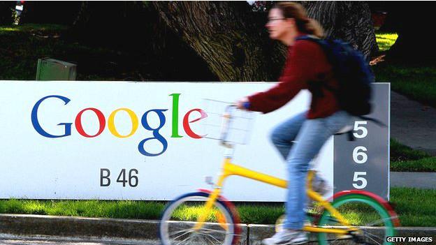 Mujer pasa en bicicleta frente a aviso de Google