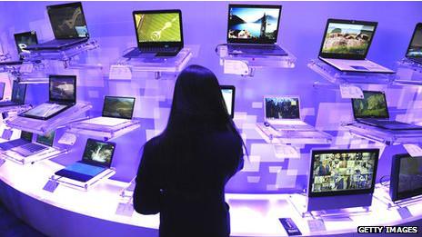 Una mujer mirando laptops en una mesa