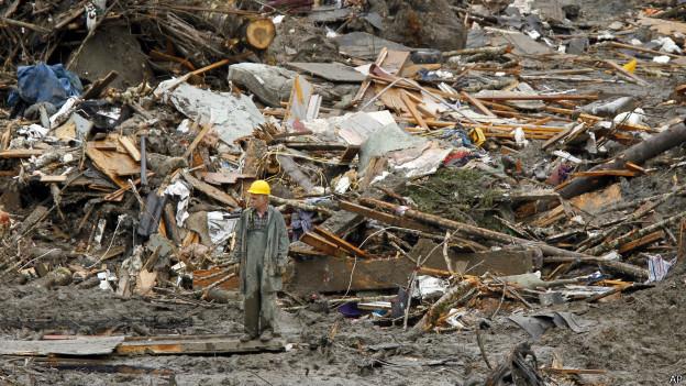 Membro de equipe de resgate caminha em cenário de deslizamento (foto: AP)