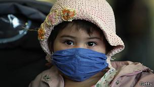Niña con tapaboca durante brote de gripe aviar