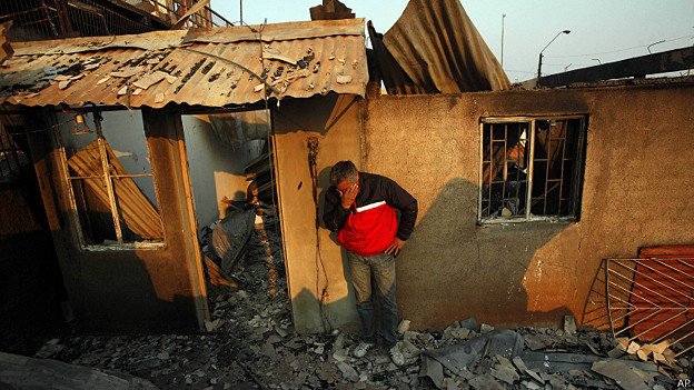 hombre solloza frente a su casa destruida por el fuego en Valparaiso, Chile