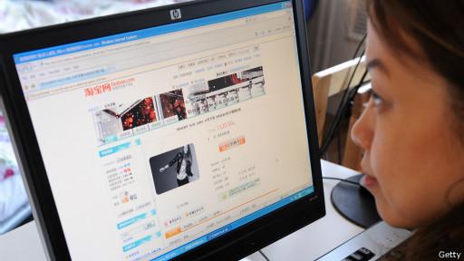 فتاة صينية تتصفح موقع تاوباو للتسوق في العاصمى بكين