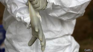 Investigador forense coloca roupa especial para coleta de material