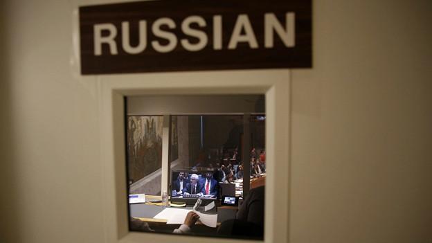 Виталий Чуркин на экране виден через окно двери кабины переводчиков ООН