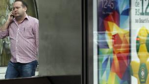 Usuário de celular diante de propaganda de operadora (Reuters)