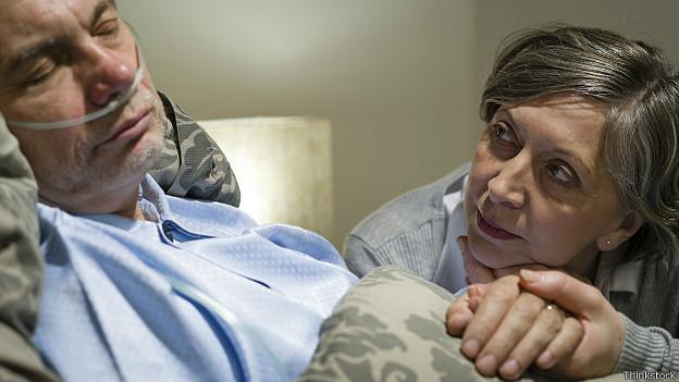 Женщина у постели больного в коме