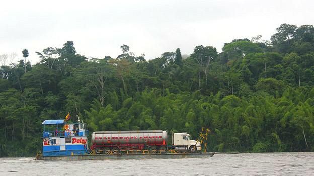 Embarcación transportando petróleo en un río amazónico