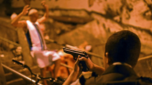 Policial aponta arma para suspeito (foto: AFP)