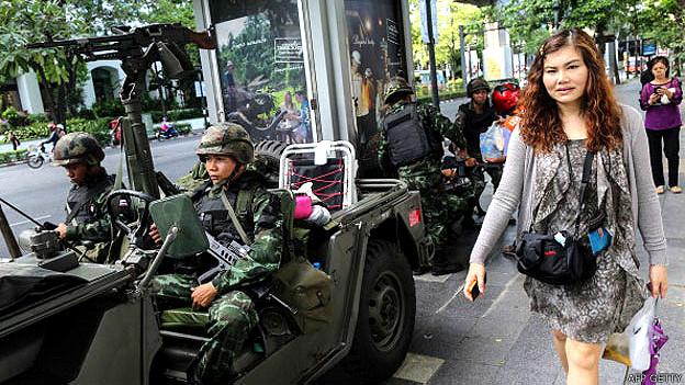 Una mujer camina junto a soldados en las calles de Bangkok