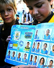 Niños en Uruguay con un album de figuritas que  muestra a los jugadores de la selección de Uruguay