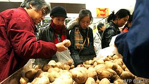 Consumidores en un mercado en Pekín comprando papas