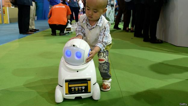 Малыш играет с домашним роботом