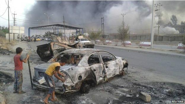 Niños junto a auto incendiado en Mosul
