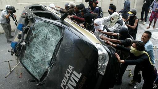 Manifestantes tumban un auto de la policía en Brasil
