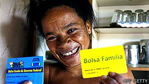 Mujer mostrando una tarjeta del programa Bolsa Familia