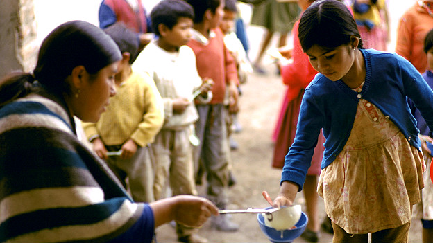 Niña recibiendo un plato de comida en Ecuador