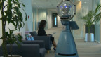 A woman sitting in a chair, next to a robot