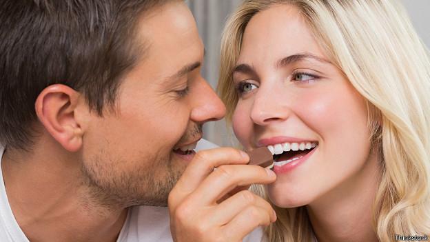 Мужчина и женщина едят конфеты