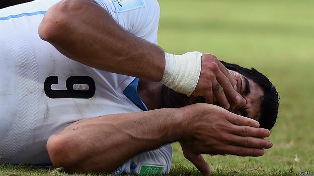 Suárez tendido y tomándose la boca tras el incidente con Chiellini