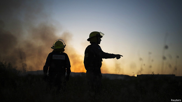 Bomberos israelíes apagan un incendio causado por un cohete de Gaza