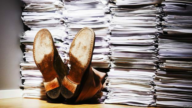 Trabajador enterrado bajo torres de papel