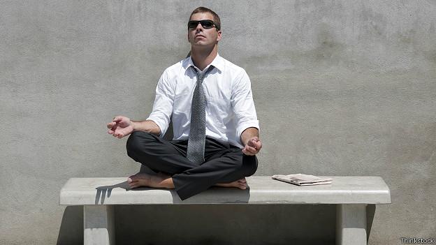 Бизнесмен медитирует на скамейке
