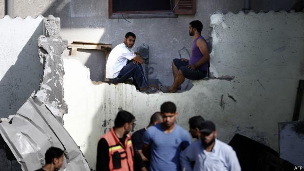 Palestinos en los restos de un edificio atacado por Israel en Jan Yunis