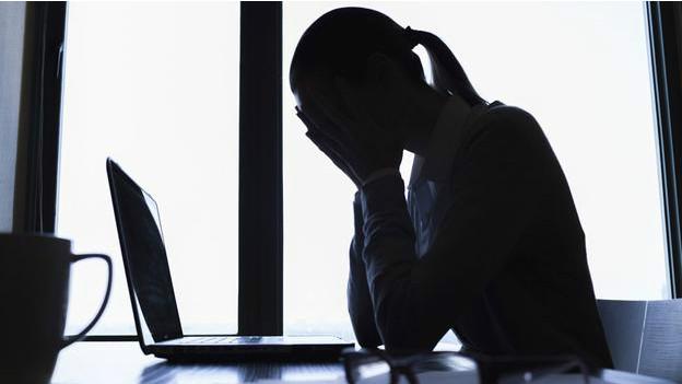 Persona triste frente a una computadora