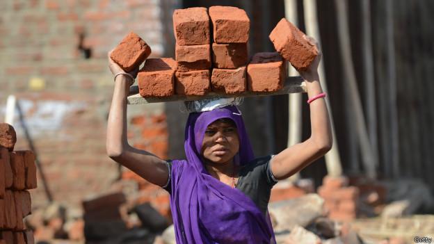 Mujer acarrea ladrillos
