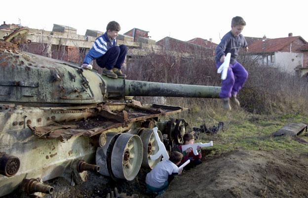 Niños jugando con un tanque en Kosovo
