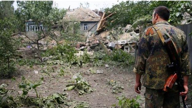 Um militante pró-Rússia olha para uma casa destruída em Snizhne, leste da Ucrânia (AFP)