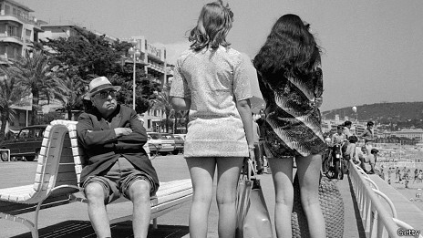 Hombre mirando con descontento a chicas en minifalda.