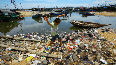 Niño salta sobre basura en la playa de Anquan, al sur de China.
