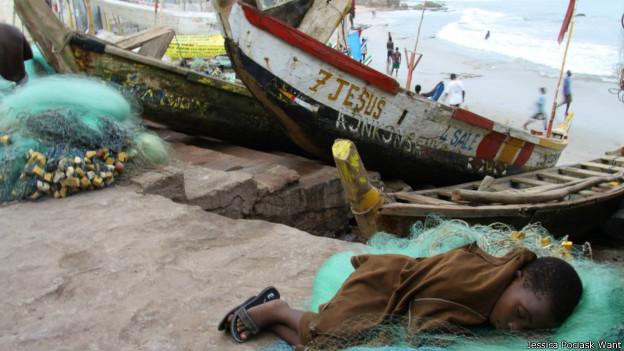 Niño descansando junto a un bote de pesca