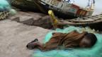 Niño descansando junto a un barco de pescadores