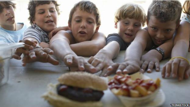 Niños ansiosos frente a comida rápida.