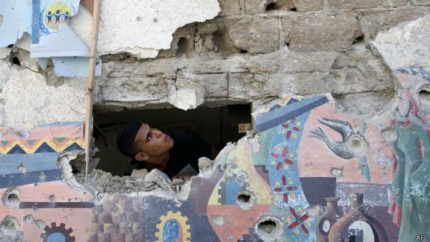Homem verifica estragos em escola atacada. Crédito: AFP