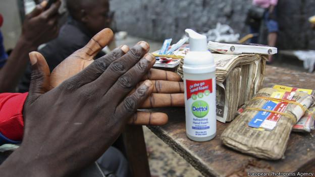 Un hombre se limpia las manos en Liberia antes de cambiar dinero a un cliente.