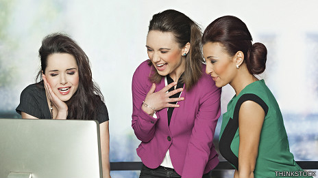 Empleadas de oficina riéndose de algo que ven en una computadora