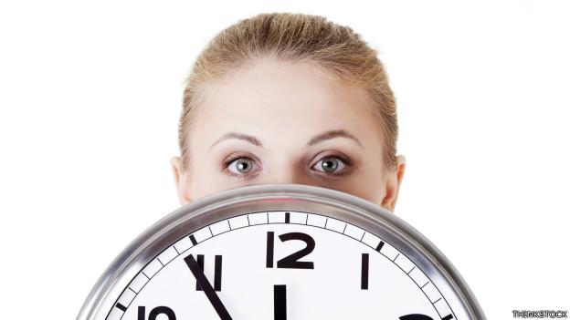Una empleada detrás de un reloj