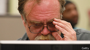 Hombre con anteojos frente a pantalla