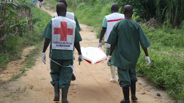 Trabajadores de la salud cargando un cadáver