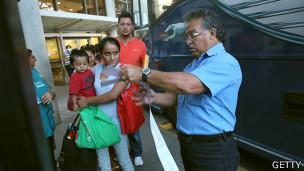 Madre y niño esperan para abordar autobús tras ser liberados de un centro de detención en EE.UU.