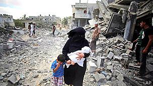 Una mujer camina con sus hijos en medio de escombros en Gaza