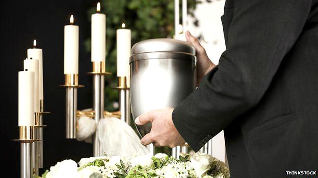 Hombre portando una urna con cenizas