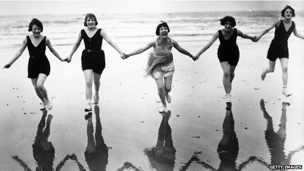En una foto antigua, jóvenes ríen en una playa