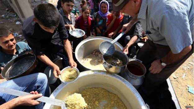 Hombre repartiendo comida entre yazidíes.