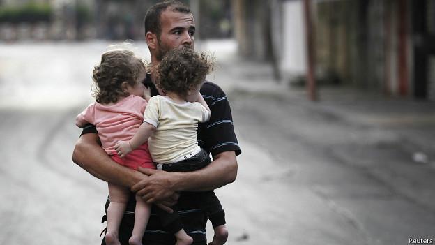 Homem carrega seus filhos em Gaza (Reuters)