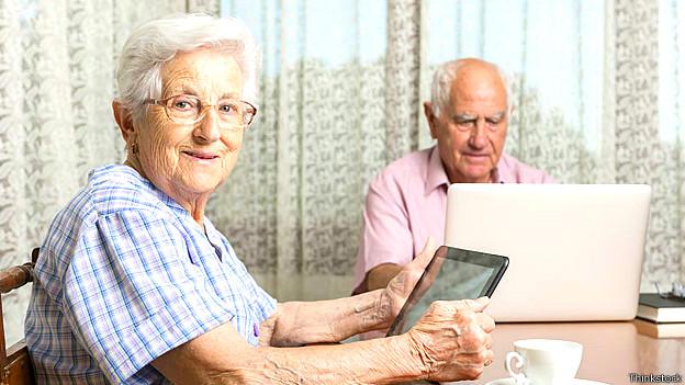 Adultos mayores usando una tableta y un computador portátil